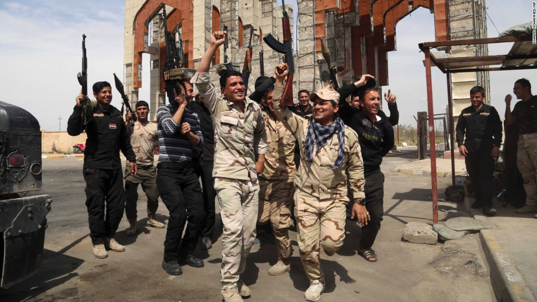 Security forces in Tikrit chant slogans against the ISIS militant group on Friday, April 3. They had just reopened the main gate of their base, which was closed for months while ISIS occupied the city.