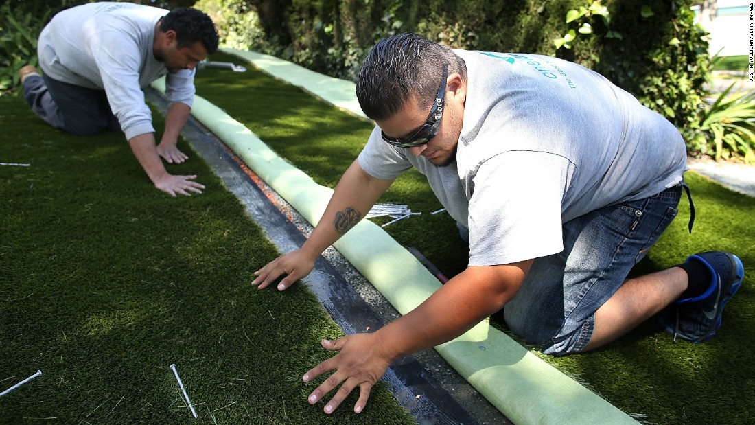 Juan Cruz and Juan Martinez of Onelawn on April 3 install a section of artificial grass at a home in Burlingame.