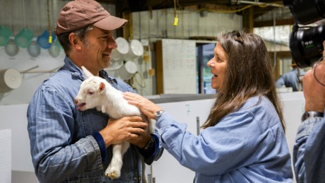 Mary Keehn teaches Mike Rowe about the goats as he holds one.