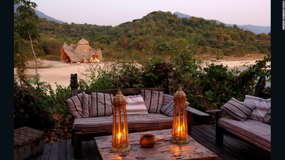 """""""The Greystoke lodge perches on a beach sandwiched between the waters of Lake Tanganyika and the forested, emerald green Mahale Mountains. This is the number one place in Africa to see chimpanzees. The lodge consists of palm-frond thatching and timbers taken from disused boats on the lake."""""""