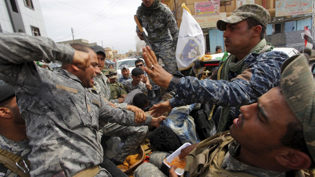A member of Iraq's security forces beats a suspected ISIS member who was captured in Tikrit on Wednesday, April 1.