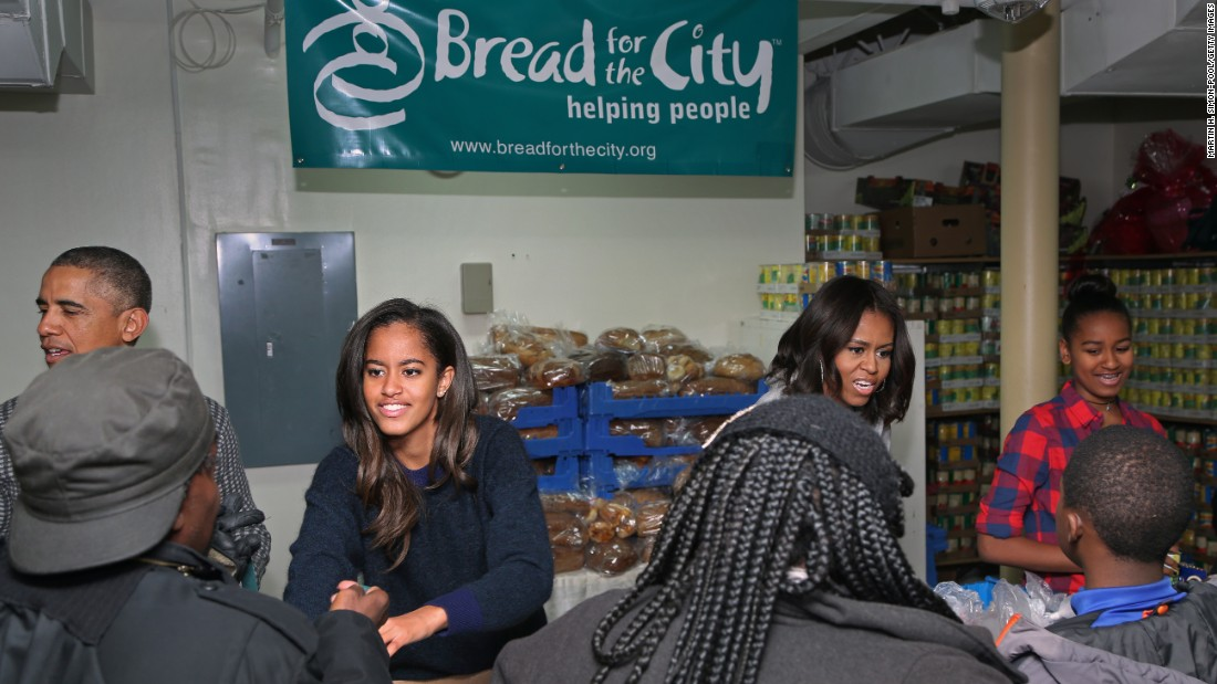 President Obama, first lady Michelle Obama and their daughters, Sasha and Malia, hand out Thanksgiving food at Bread for the City in Washington on November 26, 2014. The president and first family were participating in their annual tradition of distributing food to the needy at Thanksgiving.