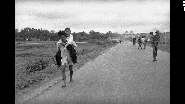More injured people walk down the road.