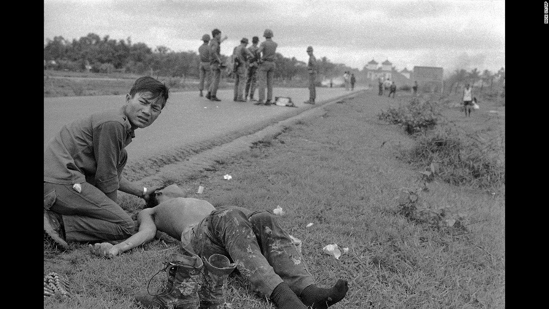 A South Vietnamese soldier crouches beside his friend who suffered severe napalm burns.