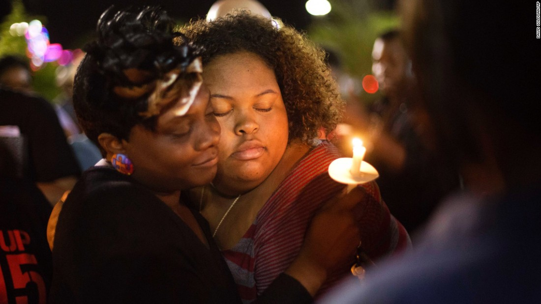 """Chasyn Carter, right, embraces Candice Ancrum during a candlelight vigil outside City Hall in North Charleston, South Carolina, on Wednesday, April 8. <a href=""""http://www.cnn.com/2015/04/08/us/south-carolina-michael-slager/index.html"""" target=""""_blank"""">Michael Slager</a>, a North Charleston police officer, has been charged with murder in the fatal shooting of <a href=""""http://www.cnn.com/2015/04/08/us/south-carolina-who-was-walter-scott/index.html"""" target=""""_blank"""">Walter Scott</a>, an unarmed 50-year-old. Video captured by a bystander showed Slager shooting Scott as he ran away."""