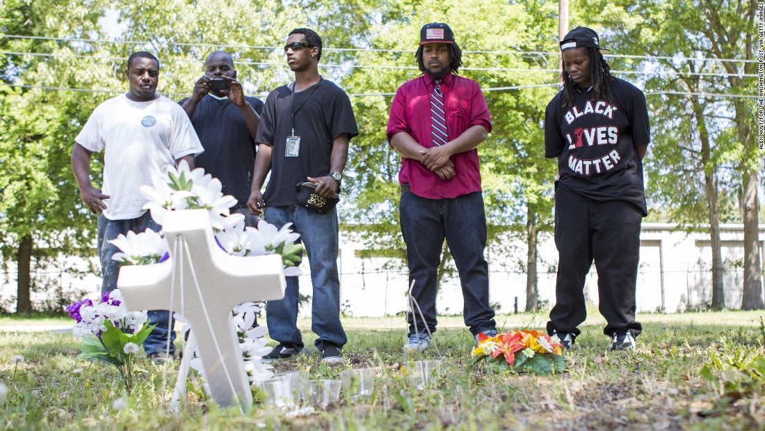 Darrell Mikell, from left, Aaron Moses, Justin Lewis and Quin Dalton stand April 8 near the site where Scott was shot and killed. The person in the background is unidentified.