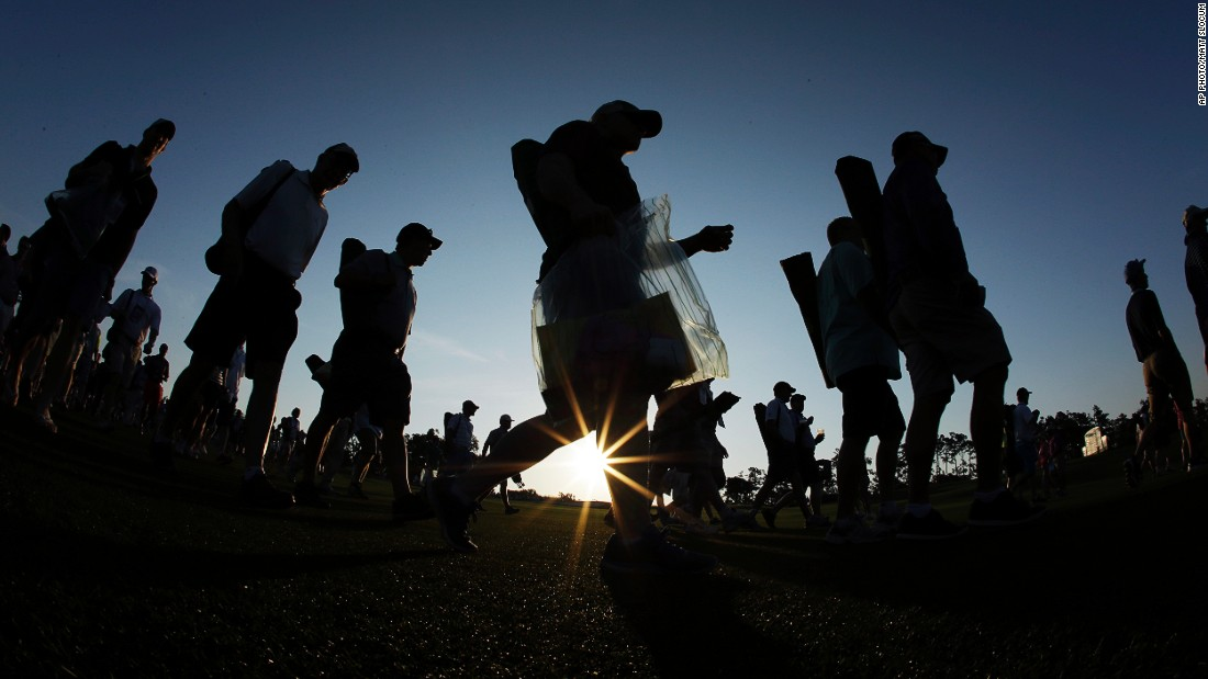 APRIL 9 - GEORGIA, UNITED STATES: Spectators walk along the first fairway before the first round of the revered Masters golf tournament at Augusta, which begins today.