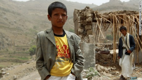 Caption:A Yemeni boy stands in front of a damaged house in the village of Bani Matar, 70 kilometers (43 miles) West of Sanaa, on April 4, 2015, a day after it was reportedly hit by an airstrike by the Saudi-led coalition against Shiite Huthi rebel positions. A Saudi-led coalition pounded rebels in southern Yemen and dropped more arms to loyalist fighters as the UN Security Council prepared to discuss calls for 'humanitarian pauses' in the air war. AFP PHOTO / MOHAMMED HUWAIS (Photo credit should read MOHAMMED HUWAIS/AFP/Getty Images)