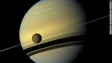A giant of a moon appears before a giant of a planet undergoing seasonal changes in this natural color view of Titan and Saturn from NASA's Cassini spacecraft.