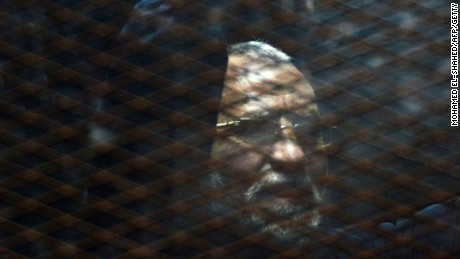 Caption:Egyptian Muslim Brotherhood leader Mohamed Badie stands behind bars during his trial at the non-commissioned police officers institute in the capital Cairo on 28 February, 2015. The court sentenced Badie to life imprisonment over the killing of protesters who stormed the group's Cairo headquarters in 2013. Three co-defendants of Badie were sentenced to death in the same trial. AFP PHOTO/ MOHAMED EL-SHAHED (Photo credit should read MOHAMED EL-SHAHED/AFP/Getty Images)