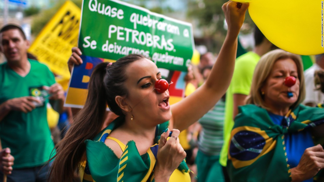 "Many demonstrators wore the country's colors -- green, blue and yellow -- waved flags, and chanted: ""Out Dilma."""
