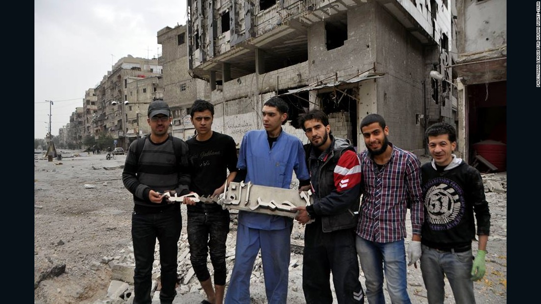 """The Palestine hospital -- the only functional hospital in the camp -- was hit by a barrel bomb, witnesses say. Here, civilians and volunteers hold up the """"Palestinian Red Crescent"""" sign that was knocked off the building by the blast."""