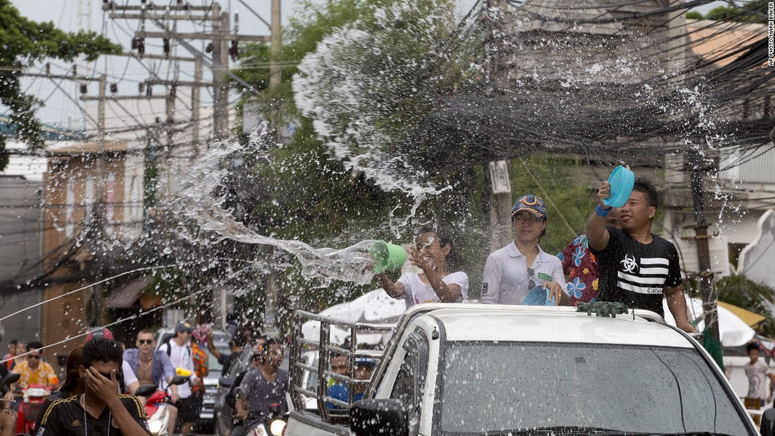Locals in the back of pickup trucks throw water at pedestrians to celebrate the Thai new year on Koh Samui, an island in Thailand's Surat Thani province.