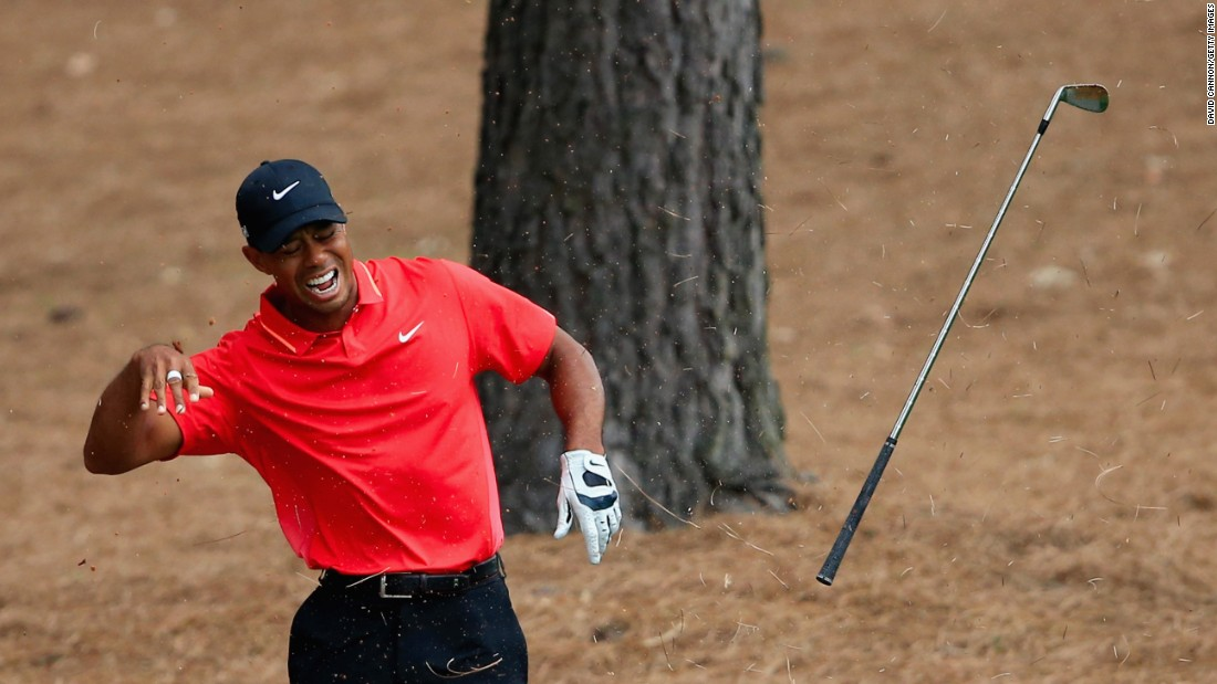 Woods winces in pain after striking a tree root with his club after a shot from the rough in the final round of the 2015 Masters Tournament in April. He finished tied for 17th.