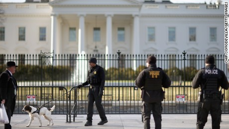 A US Secret Service K-9 team works along the second, temporary fence on the north side of the White House March 18, 2015 in Washington, DC