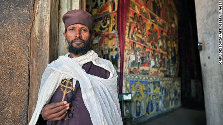 An Ethiopian Orthodox Christian monk poses while holding a cross at Ure Kidane Mihret monestary at Lake Tana in Bahar Dar, Ethiopia, on January 17, 2012. Ethiopian monks and priests are preparing for the annual festival of Timkat which celebrates the Baptism of Jesus in the Jordan River. The festival will begin on January 19. During Timkat, the Tabot, a model of the Ark of the Covenant is taken out of every Ethiopian church for 24 hours and paraded during a procession in towns across the country. Over 80 per cent of Ethiopians are estimated to be Orthodox Christians. Ethiopian Orthodox Christians believe the real Ark of the Covenant (a vessel containing the Ten Commandments) is held in Aksum, a city in Northern Ethiopia. It is guarded by a select group of monks, whose sole commitment is to protect the sacred vessel.