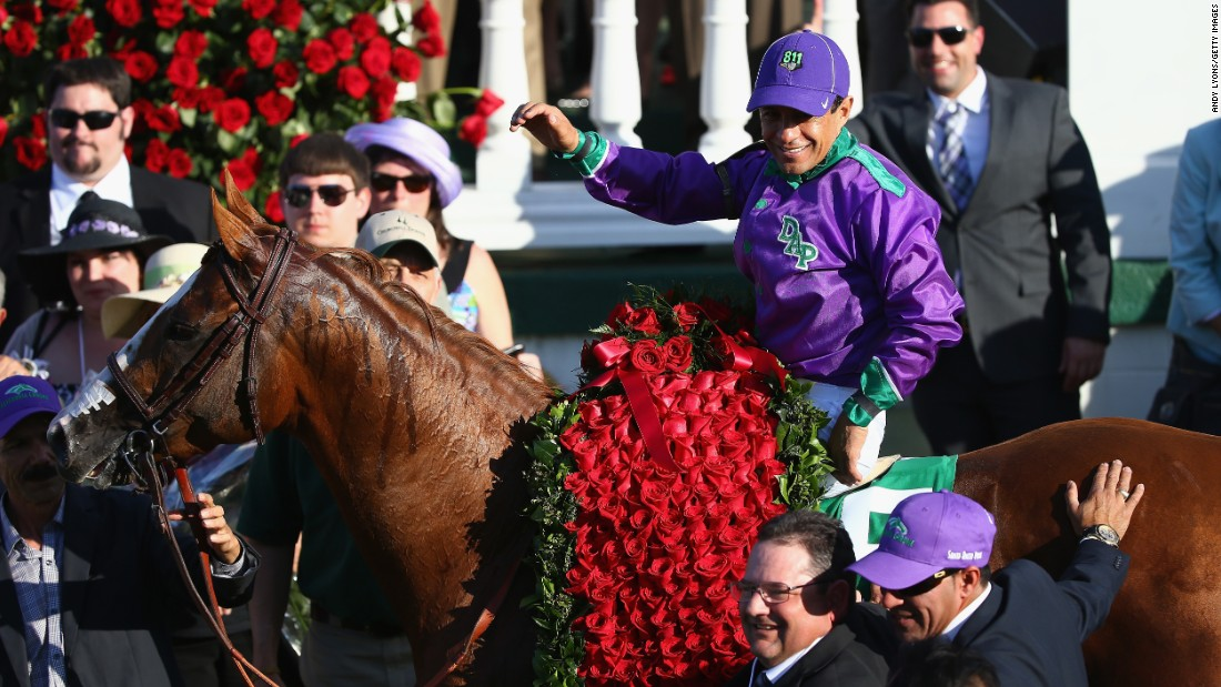 Victor Espinoza celebrates in the winner's circle after riding California Chrome (wearing a traditional victor's blanket of 554 red roses) at the 2014 Kentucky Derby. He will attempt to repeat his win this year with  American Pharoah.