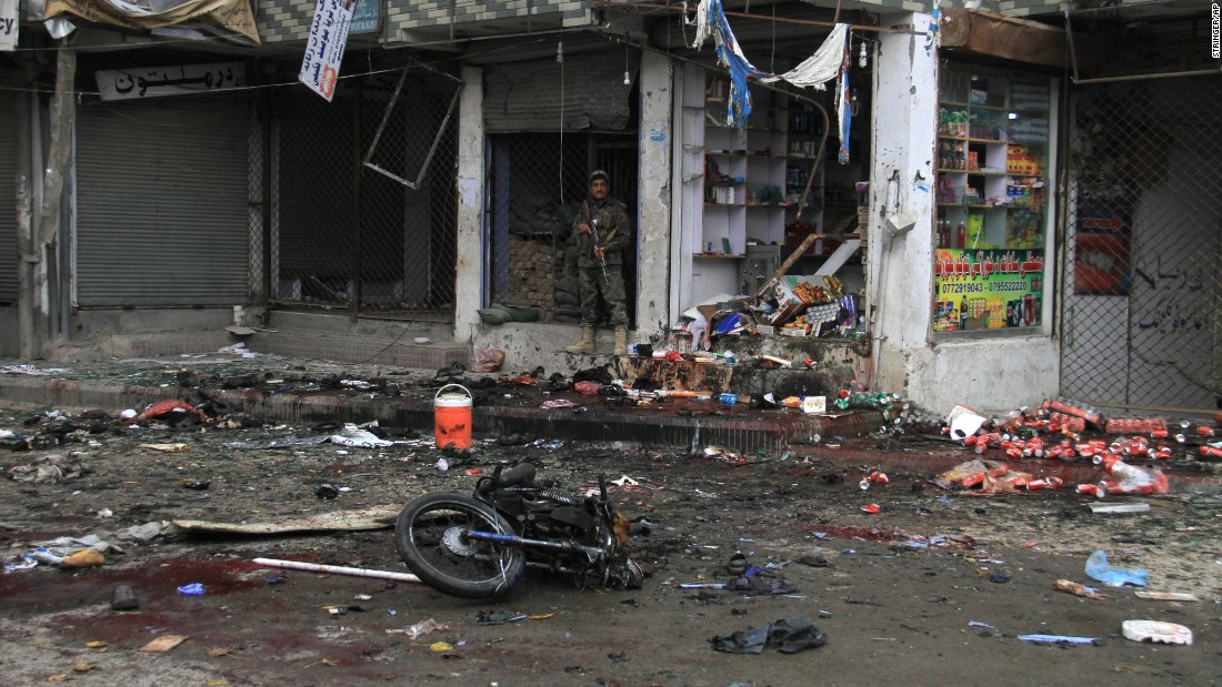 A member of the  Afghan security forces stands at the site  where a suicide bomber on a motorbike blew himself up in front of the Kabul Bank in Jalalabad, Afghanistan, on Saturday, April 18. The ISIS terrorist group claimed responsibility for the attack. The explosion killed at least 33 people and injured more than 100 others, public health spokesman Najibullah Kamawal said.