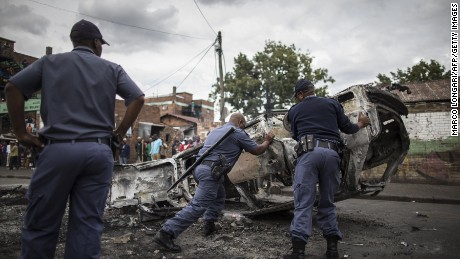 Policemen move a burnt car as angry Zulu protesters demonstrate against foreign migrants in Johannesburg on April 17, 2015.