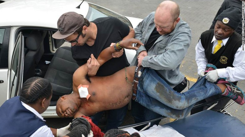 Another photographer, Antoine de Ras, captured the moment Oatway and local authorities assisted the victim. Oatway is the one holding Sithole's belt.