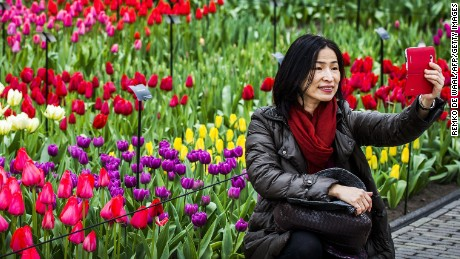 A woman poses for a selfie in front a field of tulips in the Keukenhof flower garden, also known as the Garden of Europe, in Lisse, The Netherlands, on March 21, 2015. Keukenhof is the second largest flower garden in the world.