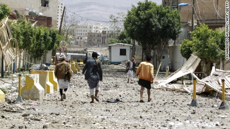 Caption:Yemenis walk along a damaged street following a raid by Saudi-led coalition warplanes on a nearby missile depot on Fajj Attan hill, in the rebel-held part of the Yemeni capital, in southern Sanaa, on April 20, 2015. AFP PHOTO / MOHAMMED HUWAIS (Photo credit should read MOHAMMED HUWAIS/AFP/Getty Images)