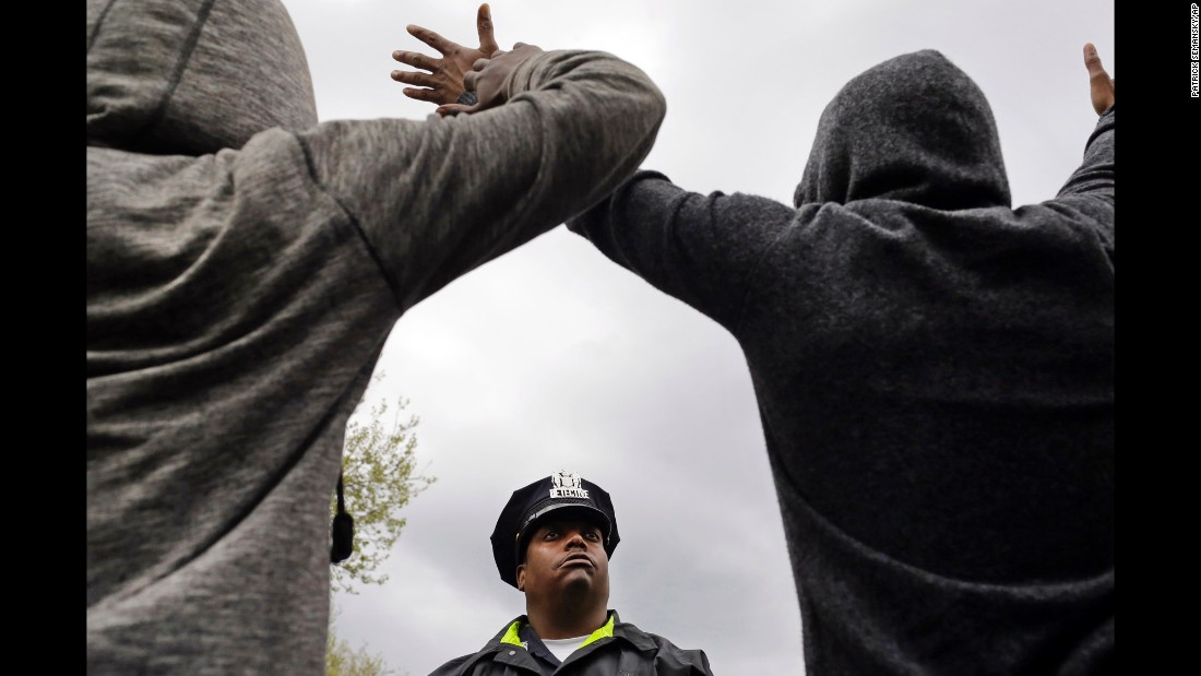 A member of the Baltimore Police Department stands guard outside the Western District station as men hold their hands up in protest on April 22.