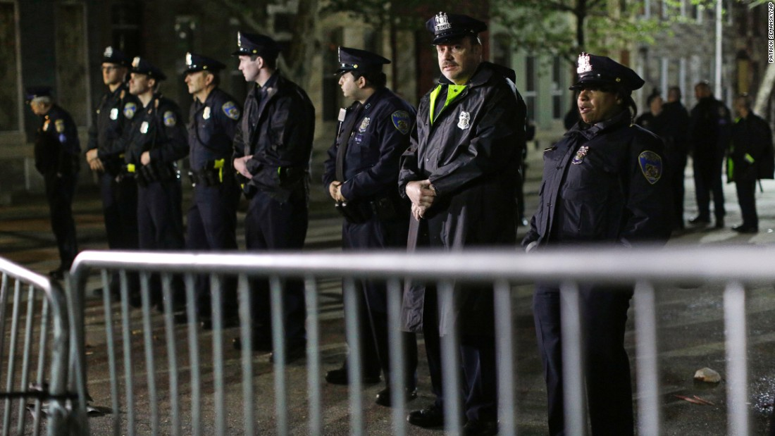 Baltimore Police stand guard behind a barrier outside the Western District station.
