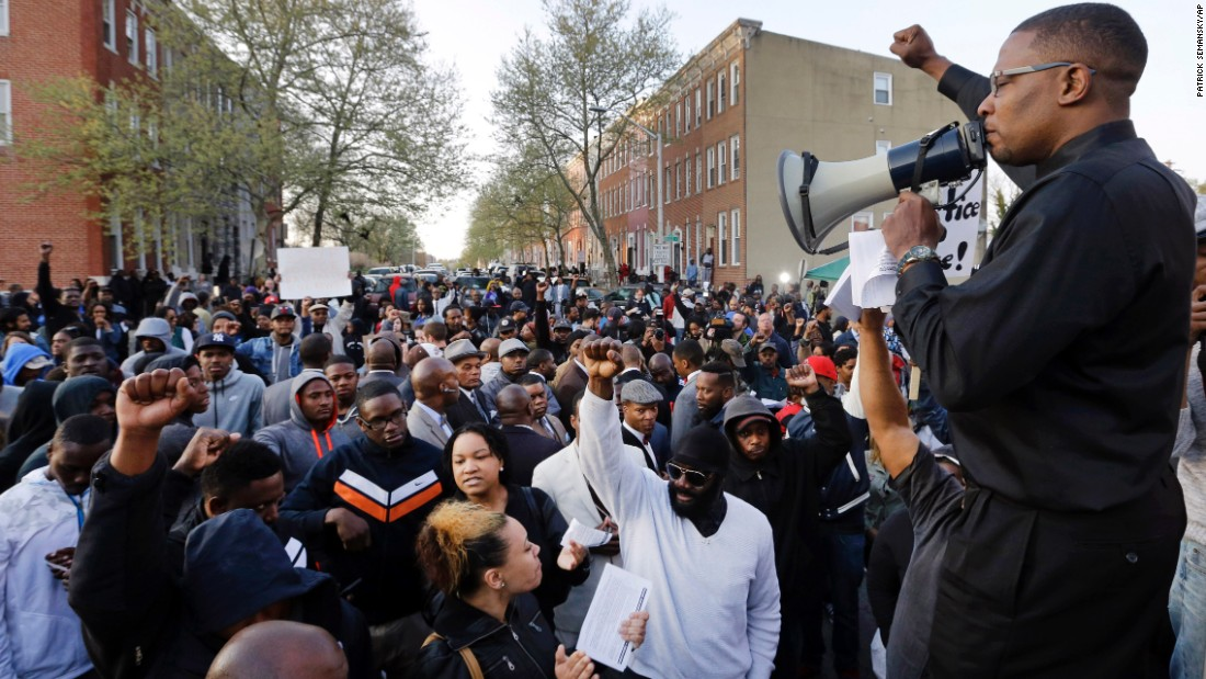 Malik Z. Shabazz, of Black Lawyers for Justice, speaks to a group of protesters outside the Western District police station.