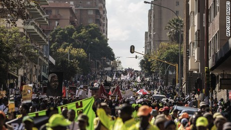 """Thousands march against the recent wave of xenophobic attacks in South Africa through the streets of Johannesburg CBD on April 23, 2015. Several thousand demonstrators marched through central Johannesburg to protest against a spate of deadly attacks on immigrants, after further raids by the authorities on suspected gang hideouts. Watched by police, crowds sang songs denouncing xenophobia and carried banners that read """"We are all Africans"""" as migrant workers crowded balconies, shouting their support. AFP PHOTO/GIANLUIGI GUERCIAGIANLUIGI GUERCIA/AFP/Getty Images"""