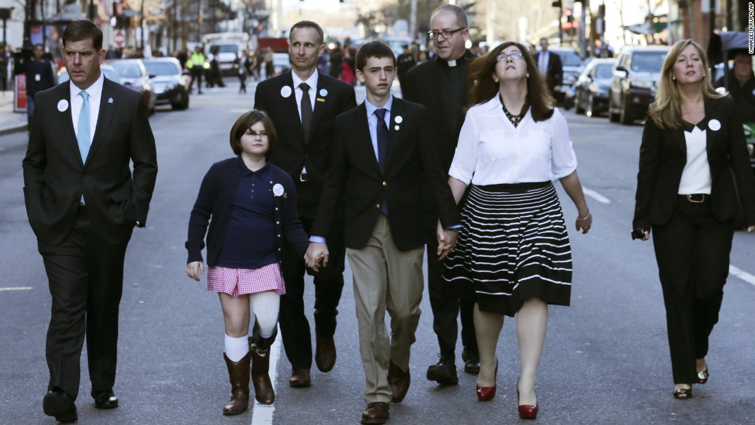 <strong>Jane Richard</strong>, in the pink skirt, lost her leg. She holds the hand of her brother Henry as they walk down Boylston Street with their parents and others after an April 15 ceremony this year. She was standing next to her brother Martin behind a metal barricade when the second bomb went off. Her father, Bill, took one look at Martin, knew he wouldn't make it and focused his efforts on saving Jane. She sang in April at Fenway Park on opening day.