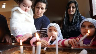 Assyrian Christian women and their daughters, refugees from the unrest in Syria, attend a prayer service at a Lebanese church northeast of Beirut. The service was for 220 Assyrian Christians abducted from their villages in northeastern Syria by Islamic State militants.