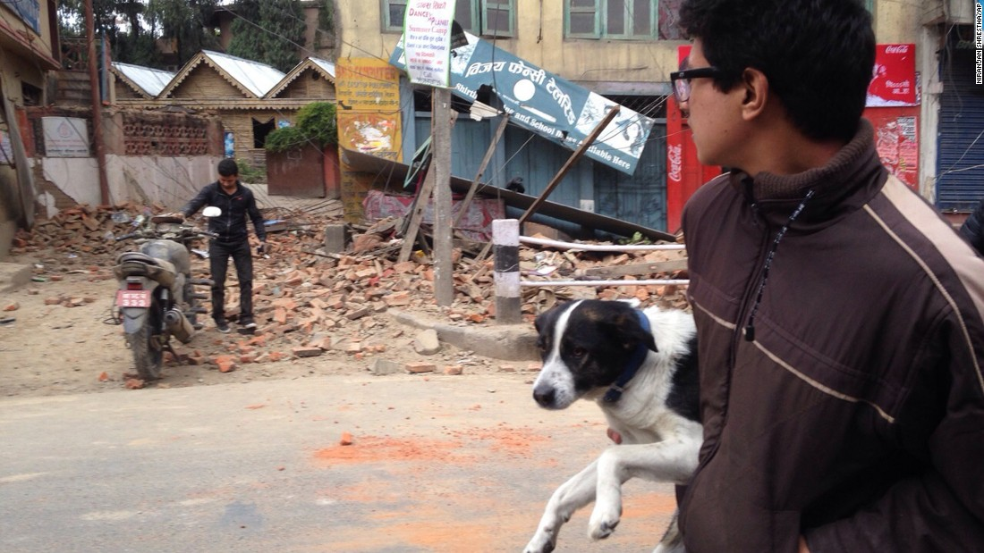 A man carries his dog past earthquake damage in Kathmandu.