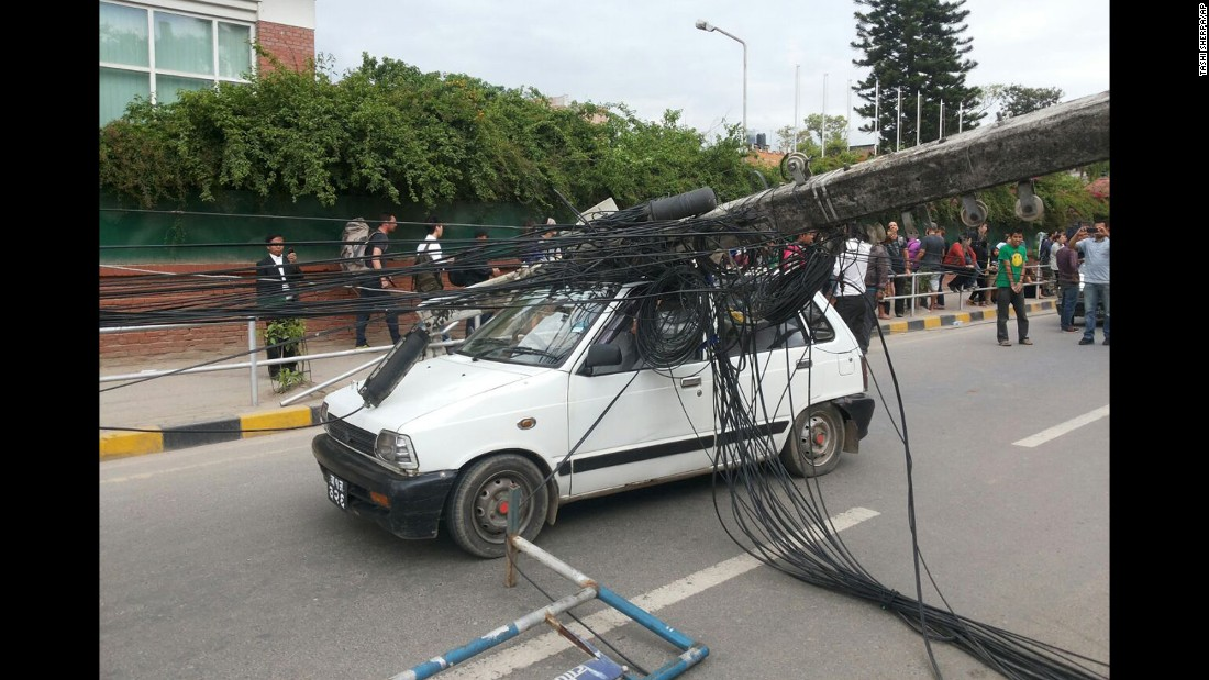 An utility pole lies on top of a vehicle in Kathmandu.