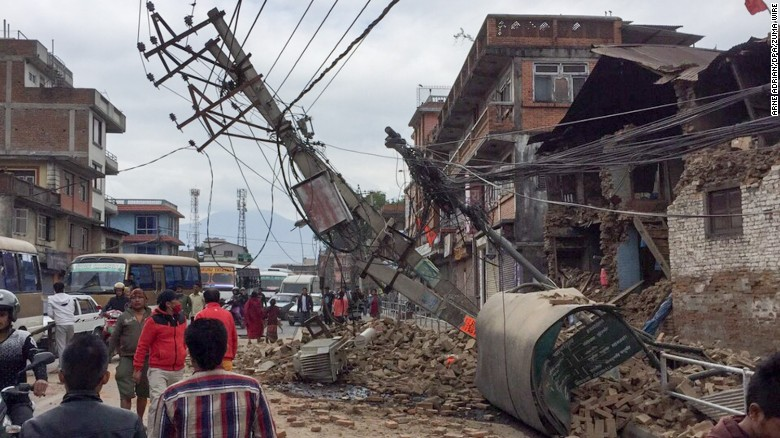 Pedestrians walk past collapsed buildings in Kathmandu, Nepal, on April 25.