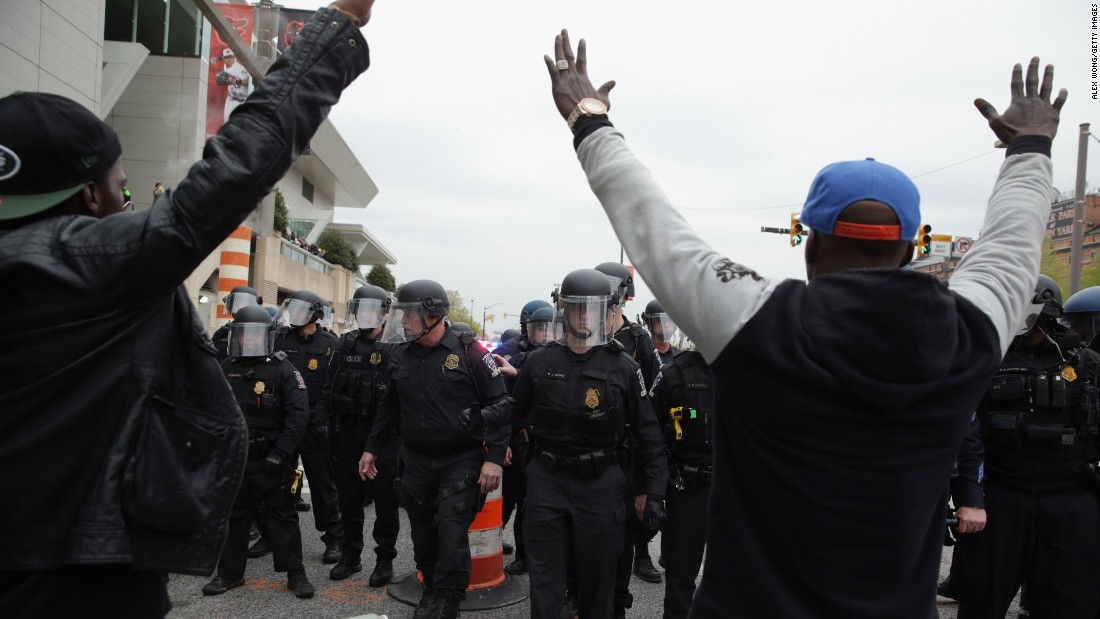 Protesters raise their hands in front of a line of police officers on April 25.