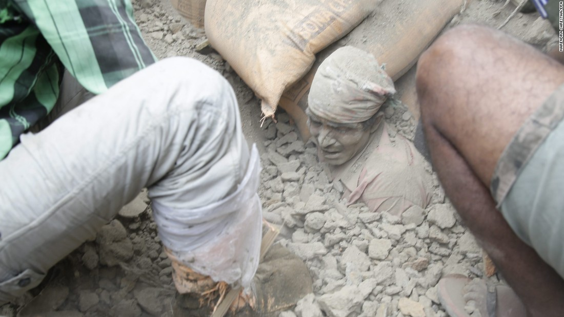 People try to free a man from the rubble in Kathmandu, Nepal, on April 25. Cheers rose from the piles when people were found alive -- but mostly bodies turned up.
