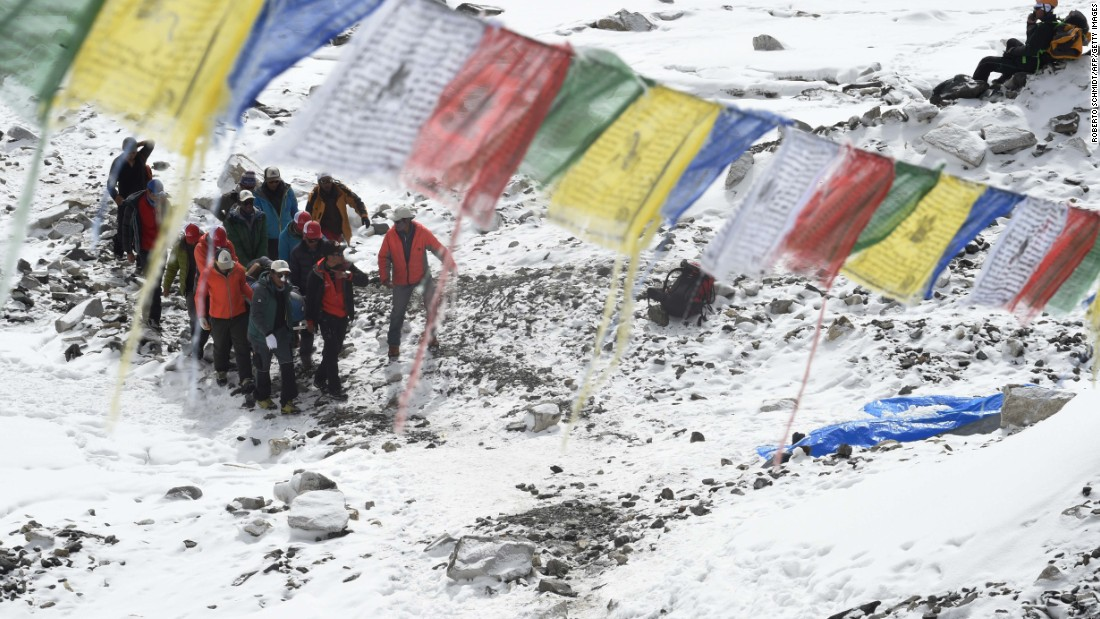 Rescue team personnel carry an injured person toward a waiting rescue helicopter on April 26 at Everest base camp.