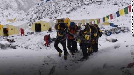 Caption:An injured person is carried by rescue members to be airlifted by rescue helicopter at Everest Base Camp on April 26, 2015, a day after an avalanche triggered by an earthquake devastated the camp. Rescuers in Nepal are searching frantically for survivors of a huge quake on April 25, that killed nearly 2,000, digging through rubble in the devastated capital Kathmandu and airlifting victims of an avalanche at Everest base Camp. The bodies of those who perished lie under orange tents. AFP PHOTO/ROBERTO SCHMIDT (Photo credit should read ROBERTO SCHMIDT/AFP/Getty Images)
