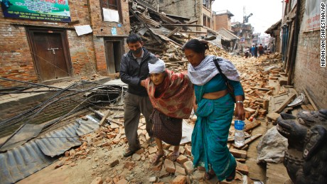 An elderly woman is helped to her home after being treated for her injuries in Bhaktapur, Nepal,  on Sunday, April 26.