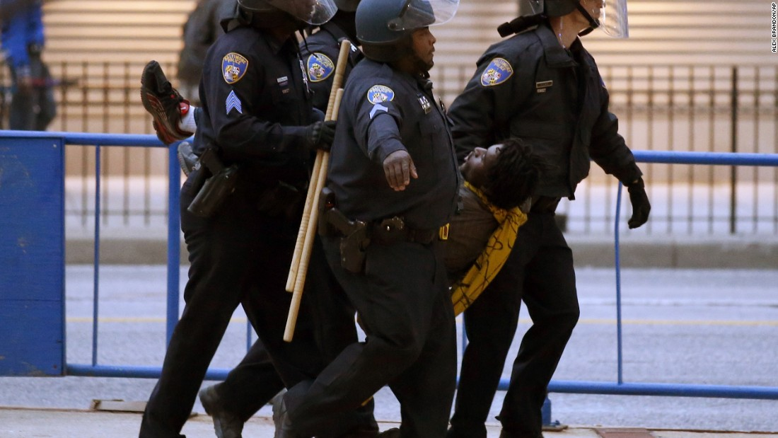 Police carry a detained man to a police van after the march to City Hall on April 25.