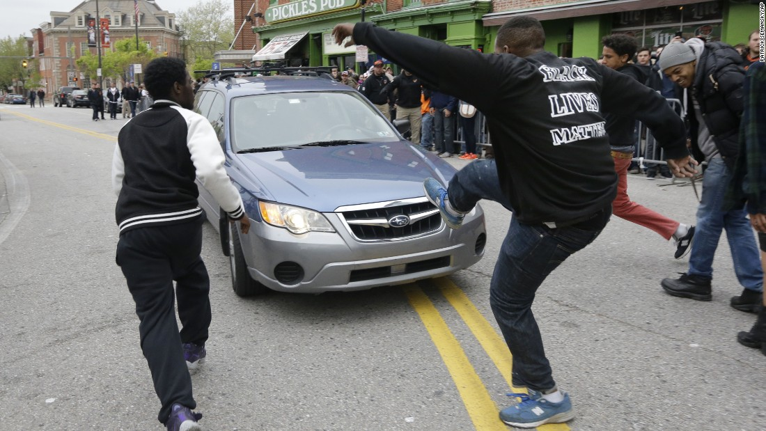 Protesters chase after a car as it drives in reverse after the rally on April 25.