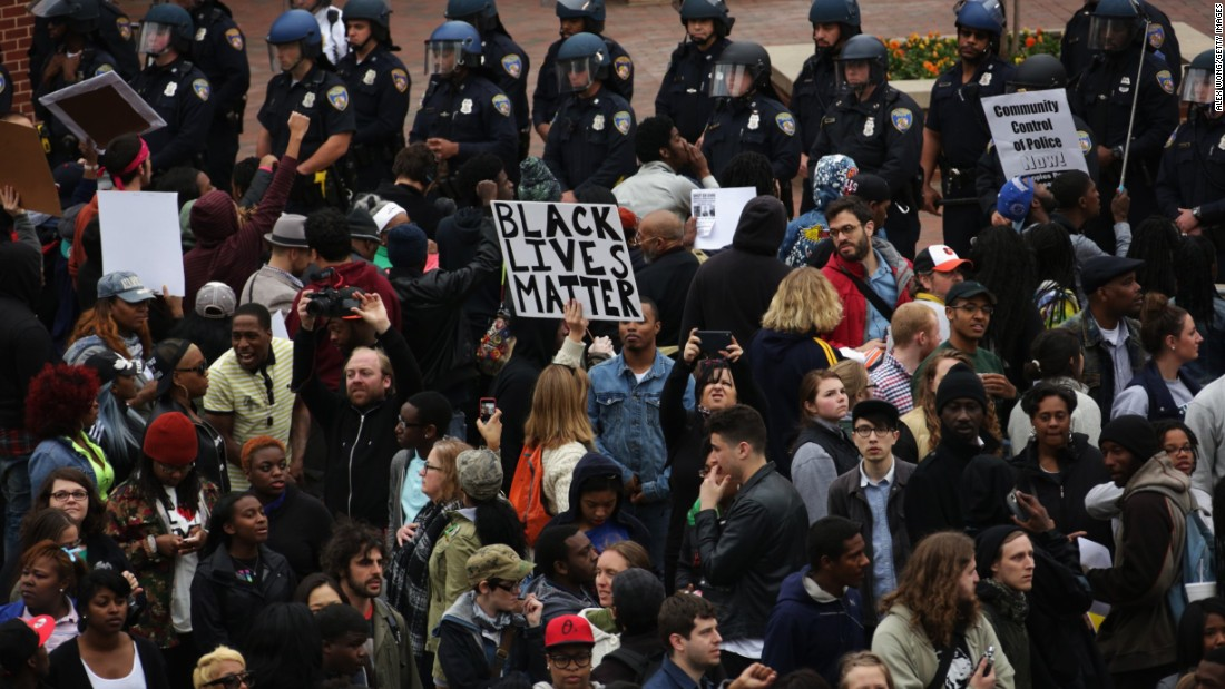 Protesters hold signs as they stand off with the police at Camden Yards during a march on April 25.