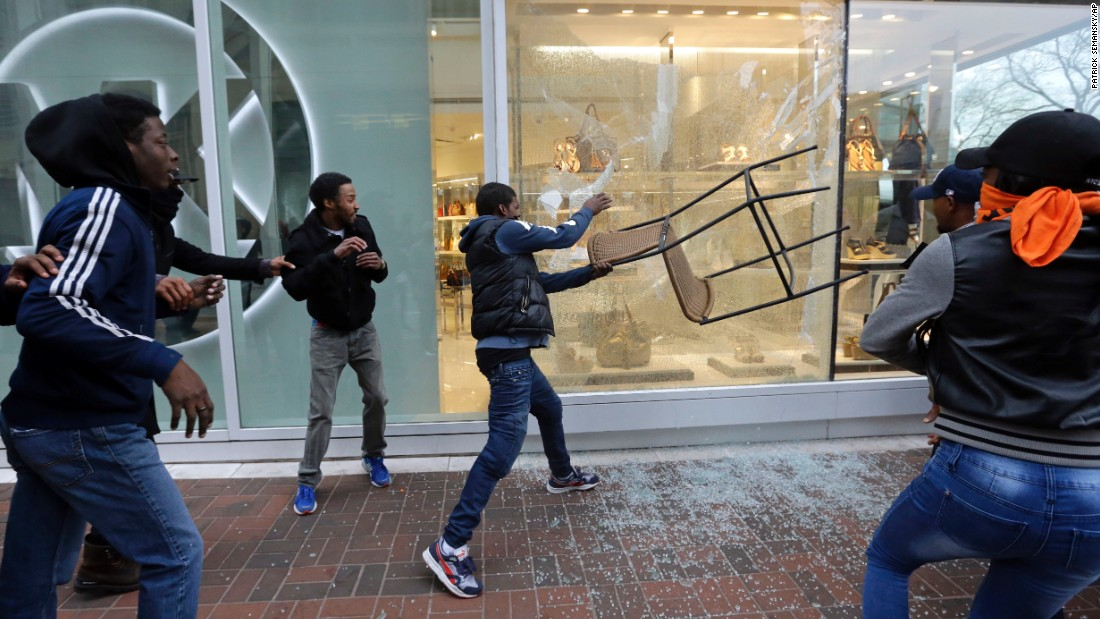 A protester breaks a store window after the rally in Baltimore on April 25.