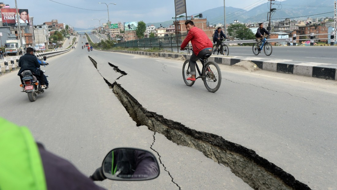 Residents cycle over damaged roads on the outskirts of Kathmandu on April 26.