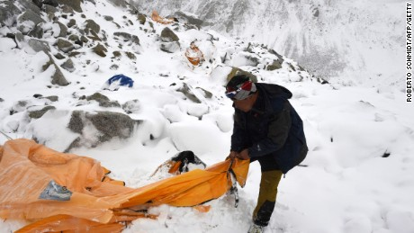 Caption:In this photograph taken on April 25, 2015, expedition guide Pasang Sherpa searches through flattened tents in search of survivors after an avalanche that flattened parts of Everest Base Camp. Rescuers in Nepal are searching frantically for survivors of a huge quake on April 25, that killed nearly 2,000, digging through rubble in the devastated capital Kathmandu and airlifting victims of an avalanche at Everest base camp. AFP PHOTO/Roberto SCHMIDT (Photo credit should read ROBERTO SCHMIDT/AFP/Getty Images)