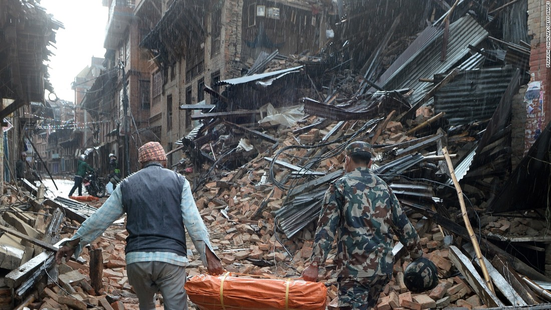 A Nepalese volunteer and a member of the security forces carry tents for distribution on the outskirts of Kathmandu on April 26.