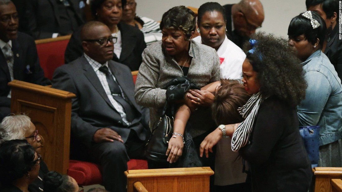 Mourners help a woman who collapsed during the funeral.