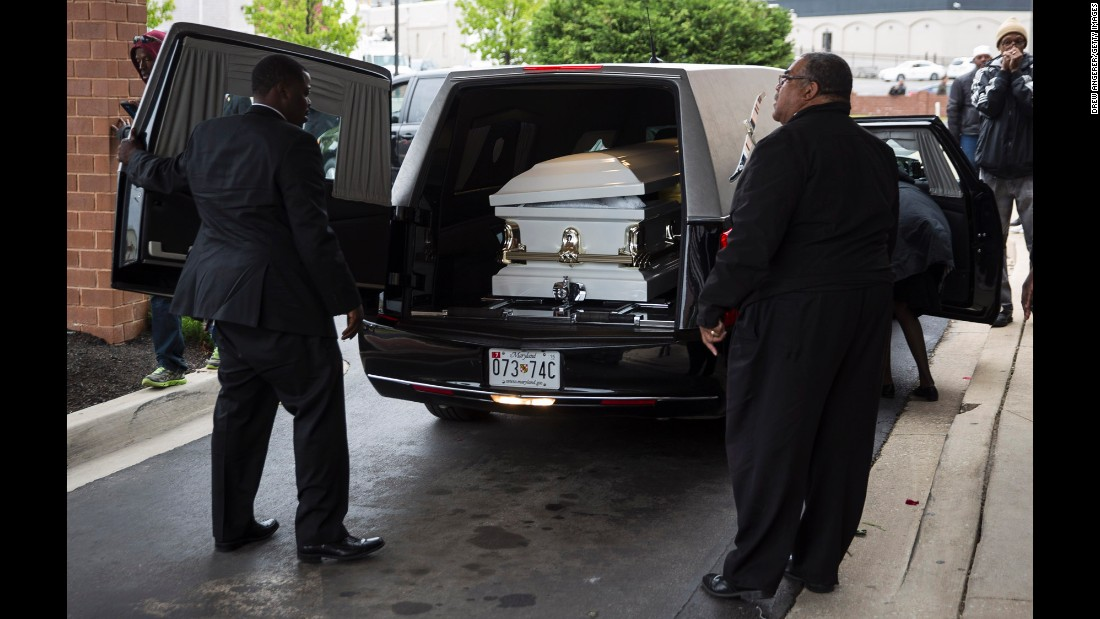 Men prepare to remove Gray's casket from the hearse in front of the church.