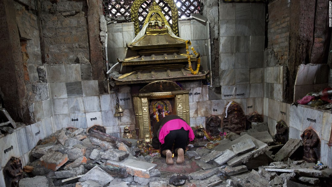 A Nepalese woman prays at a ruined temple that was damaged in Saturday's earthquake in Kathmandu on April 27.